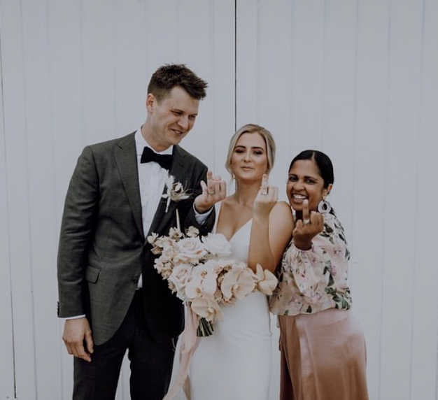 Marriage celebrant and couple showing their ring fingers