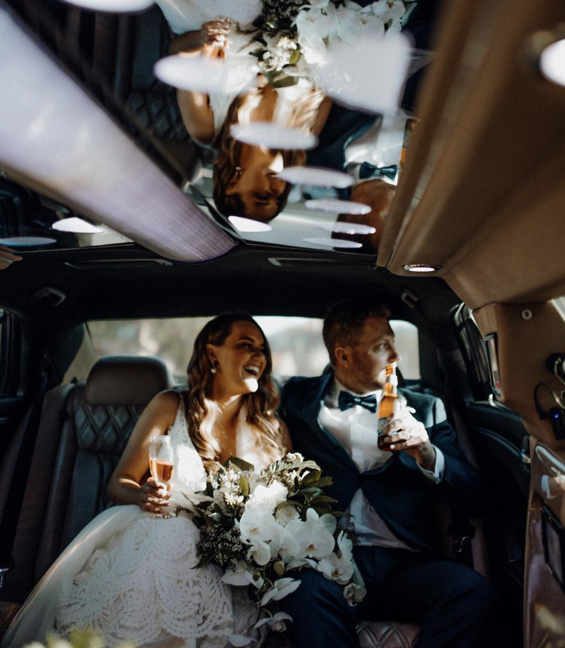 Wedding couple toasting champagne in limo